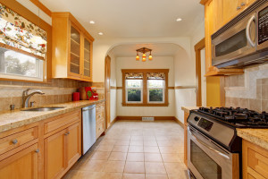 Light brown tones kitchen interior with tile floor, white ceiling and steel appliances. View of empty dining area
